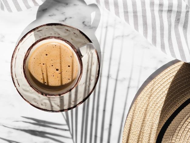 Copo branco com formas vermelhas, cheio de café cremoso em um fundo branco com um pano cinza e branco listrado coberto por uma sombra de folha de ficus e um chapéu Foto gratuita