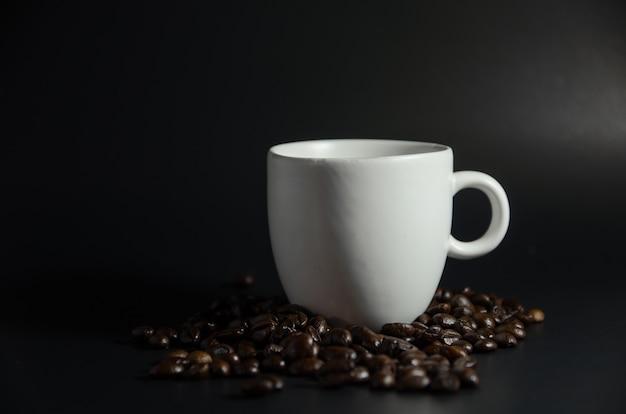 Copo branco com grãos de café na luz escura Foto Premium