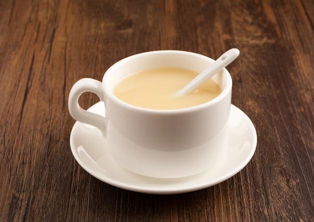 Copo branco do café sobre uma mesa de madeira Foto gratuita