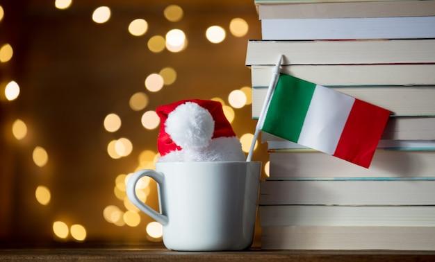 Copo branco e chapéu de natal com bandeira de itália perto de livros Foto Premium