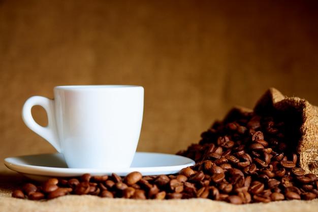 Copo branco e grãos de café na turva. Foto Premium