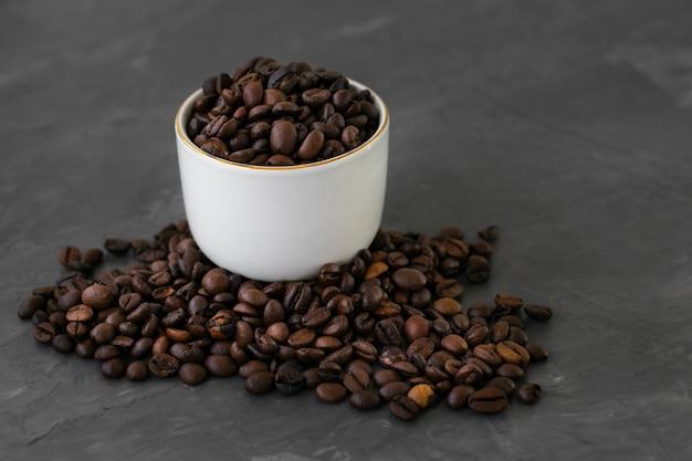 Copo cerâmico de close-up cheio de grãos de café Foto gratuita