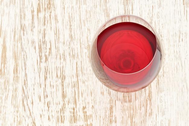 Copo cheio de vinho tinto em uma mesa de madeira branca, ângulo superior. Foto Premium