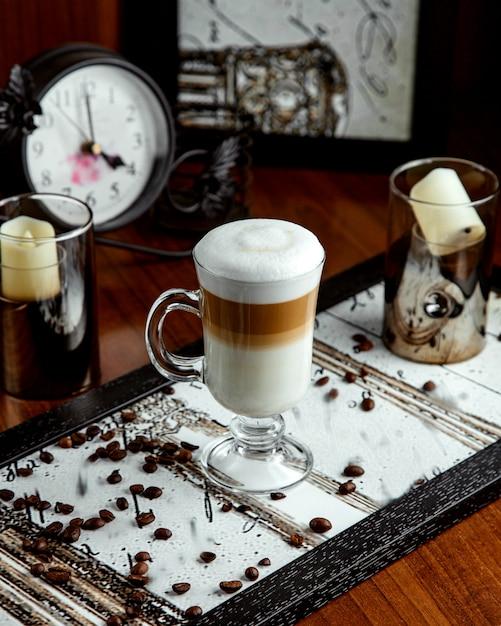 Copo com café com leite e grãos de café na mesa Foto gratuita