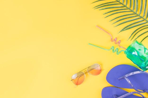 Copo com canudos perto de óculos de sol com flip-flops e folha de planta Foto gratuita