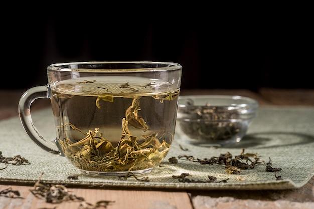 Copo com ervas de chá na mesa Foto Premium