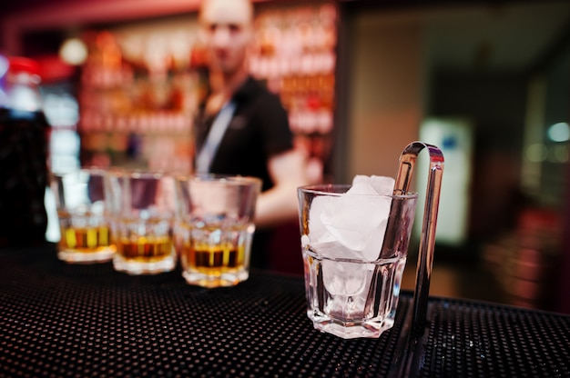 Copo com gelo e pinças com três copos de uísque barman de fundo Foto Premium