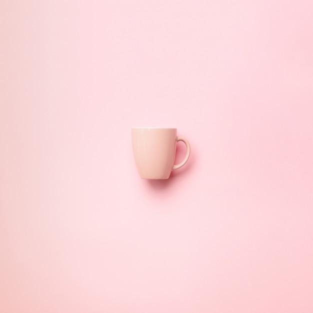 Copo cor-de-rosa sobre o fundo punchy. celebração da festa de anos, conceito do chuveiro de bebê. padrão de cores pastel. design de estilo minimalista Foto Premium