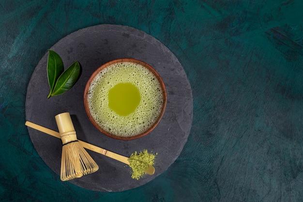 Copo da vista superior do chá verde do matcha na placa do serviço do xisto no fundo esmeralda com espaço da cópia. Foto Premium