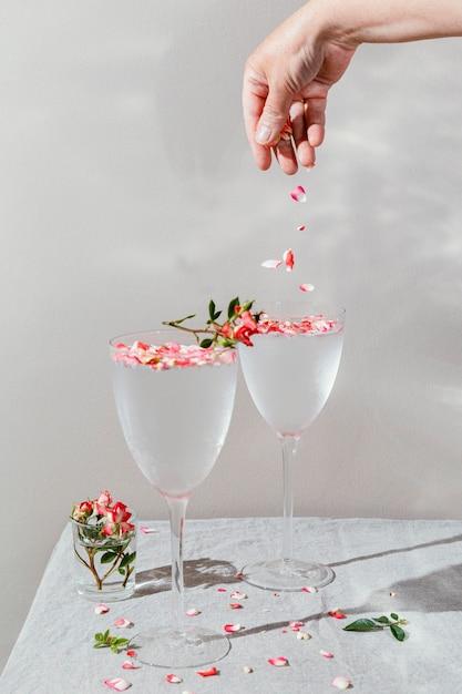 Copo de água com pétalas de flores Foto Premium