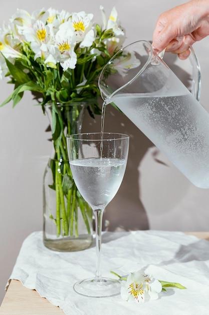 Copo de água e vaso com flores Foto Premium