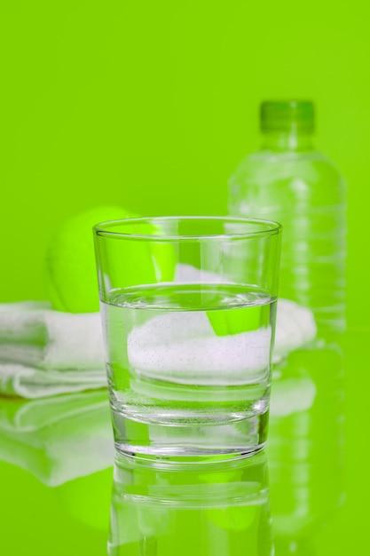 Copo de água mineral em fundo verde Foto Premium