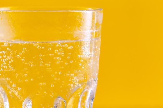 Copo de água sobre fundo amarelo. estilo de vida saudável Foto Premium
