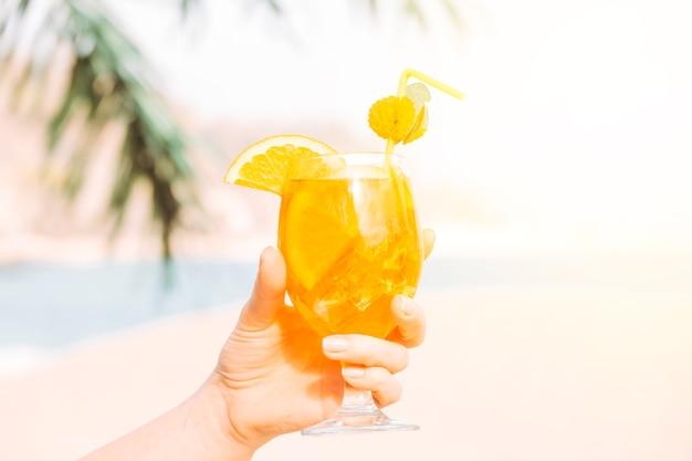 Copo de bebida aromática de laranja na mão Foto gratuita