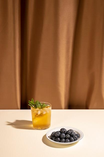 Copo de bebida caseira com mirtilos no prato sobre mesa branca perto da cortina marrom Foto gratuita