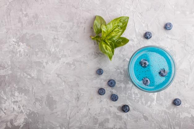 Copo de bebida colorida de mirtilo azul com sementes de manjericão, sobre um fundo cinza de concreto Foto Premium