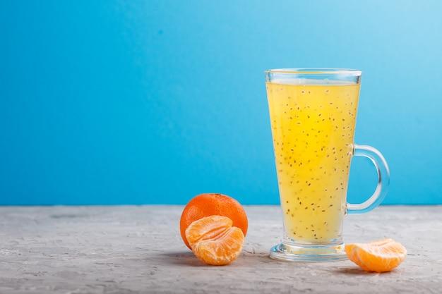 Copo de bebida colorida laranja tangerina com sementes de manjericão. vista lateral Foto Premium