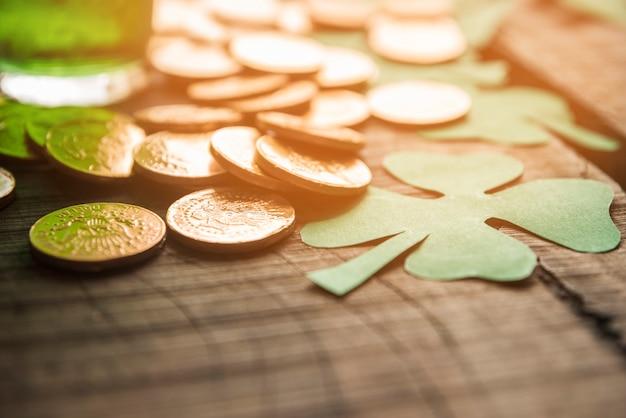 Copo de bebida verde perto de pilha de moedas e trevos de papel na mesa Foto gratuita
