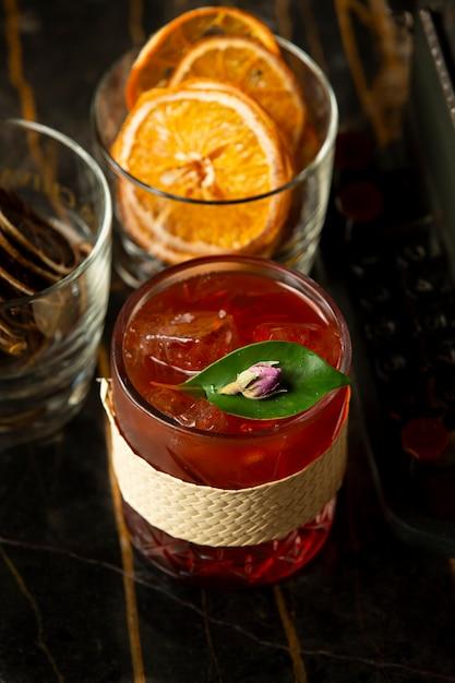 Copo de bebida vermelha com gelo decorado com licença e botão de rosa Foto gratuita