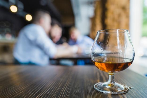 Copo de bebidas douradas na superfície de madeira no restaurante Foto gratuita