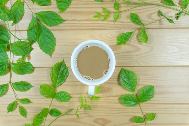 Copo de café branco cercado pelas folhas verdes em uma tabela de madeira. Foto Premium