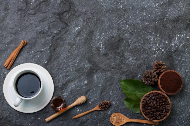 Copo de café branco leigos plana, grãos de café em copo de madeira na folha verde, açúcar em colher de madeira, pinho Foto Premium