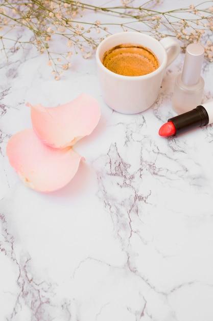 Copo de café branco; pétalas de rosa; garrafa de esmalte; flores de respiração do bebê e batom no pano de fundo texturizado branco Foto gratuita