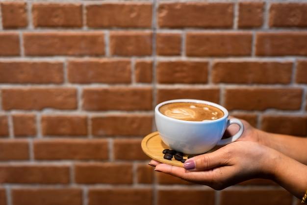 Copo de café de latte art nas mãos com fundo de parede de tijolo Foto Premium