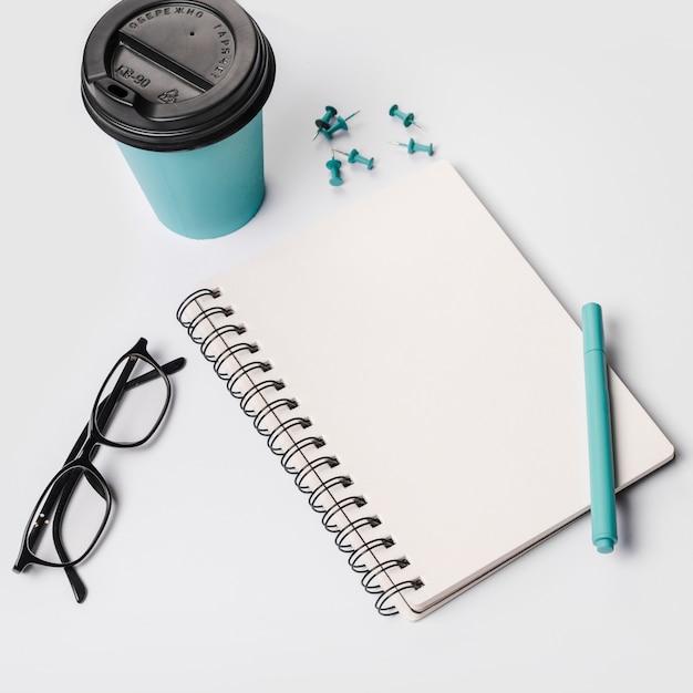 Copo de café descartável; caneta; óculos; bloco de notas em espiral; pinos de percevejo em fundo branco Foto gratuita