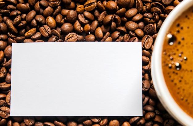 Copo de café e grãos de café na mesa, vista superior, café amor, grãos de café castanho isolado no fundo branco, copo de café quente com grãos de café Foto gratuita