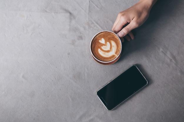 Copo de café e telefone móvel na toalha de mesa cinzenta com fundo da mancha. Foto Premium