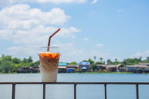 Copo de café expresso frio na varanda de ferro com vista para o rio e para a casa. Foto Premium