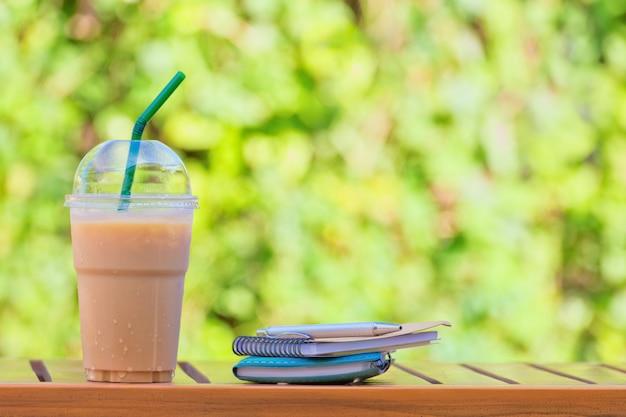 Copo de café gelado no fundo natural verde bonito. Foto Premium