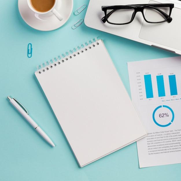 Copo de café, óculos, laptop, óculos, papel de dados, caneta e bloco de notas espiral em branco Foto gratuita