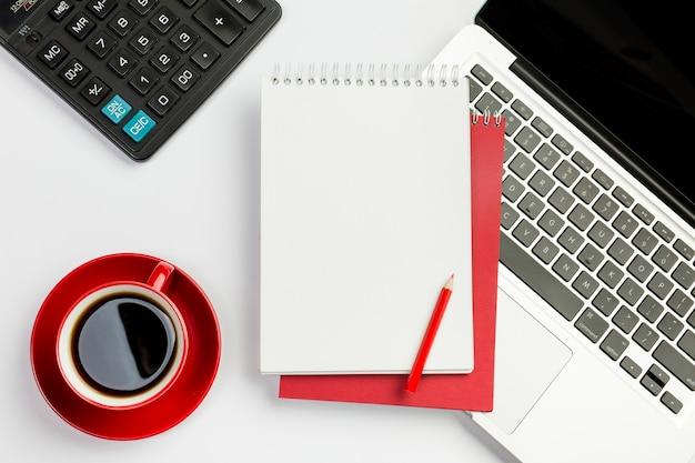 Copo de café vermelho, calculadora, bloco de notas em espiral, lápis no laptop sobre o fundo branco Foto gratuita