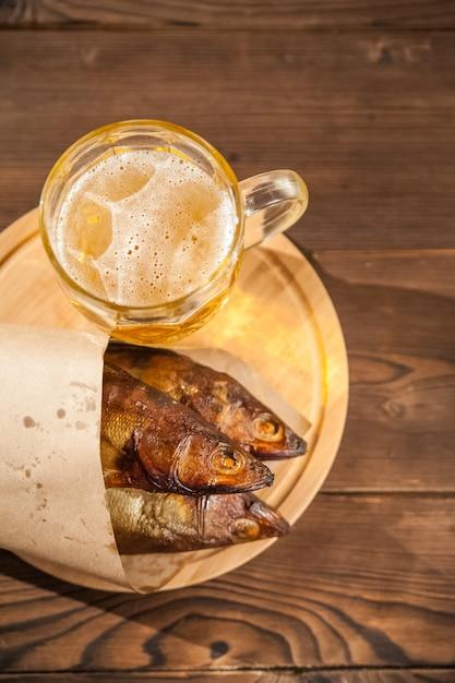 Copo de cerveja com cerveja e close-up de peixe defumado quente. caneca de cerveja com cerveja e peixe em um fundo escuro e copie o espaço. Foto Premium