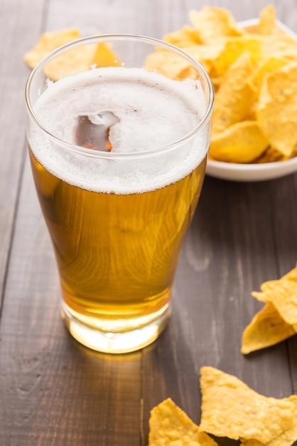 Copo de cerveja com chips de nachos em uma mesa de madeira Foto Premium