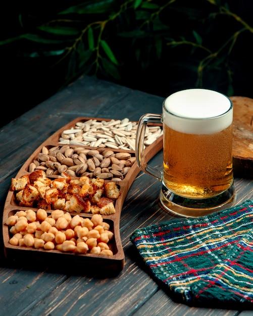 Copo de cerveja com espuma e lanches Foto gratuita