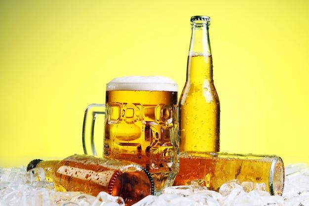 Copo de cerveja com espuma em fundo amarelo Foto gratuita