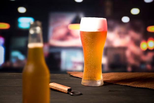 Copo de cerveja com garrafa desfocada Foto gratuita