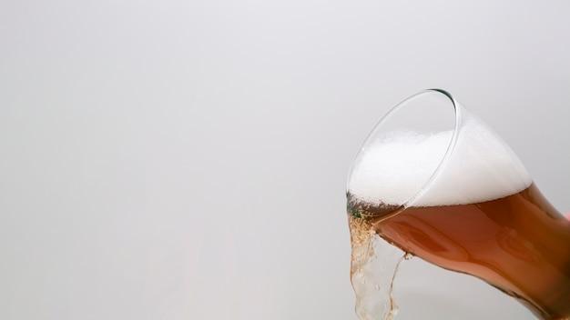 Copo de cerveja derramando com espaço de cópia Foto gratuita