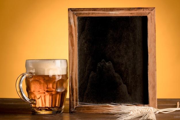 Copo de cerveja e quadro negro na mesa de madeira Foto gratuita