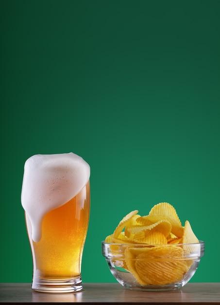 Copo de cerveja light com gotejamento de espuma e prato de batatas fritas Foto Premium