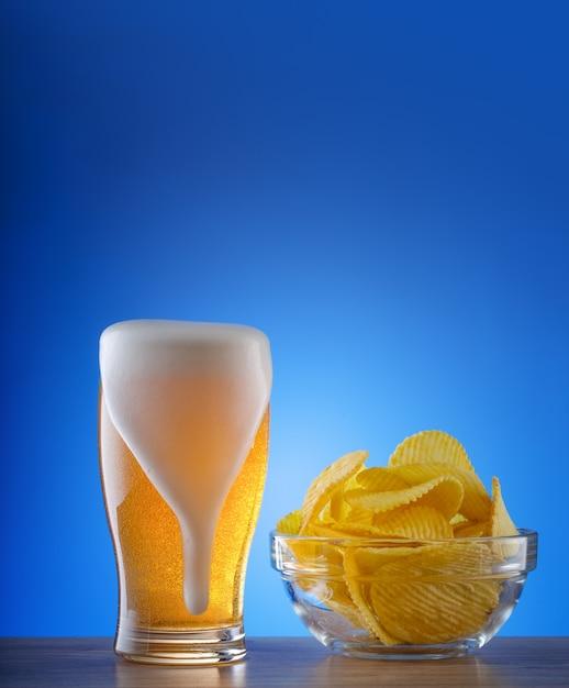 Copo de cerveja light com manchas de espuma e batatas fritas onduladas Foto Premium