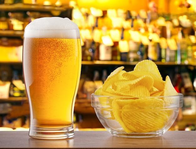 Copo de cerveja light e batatas fritas no balcão de bar em bar Foto Premium