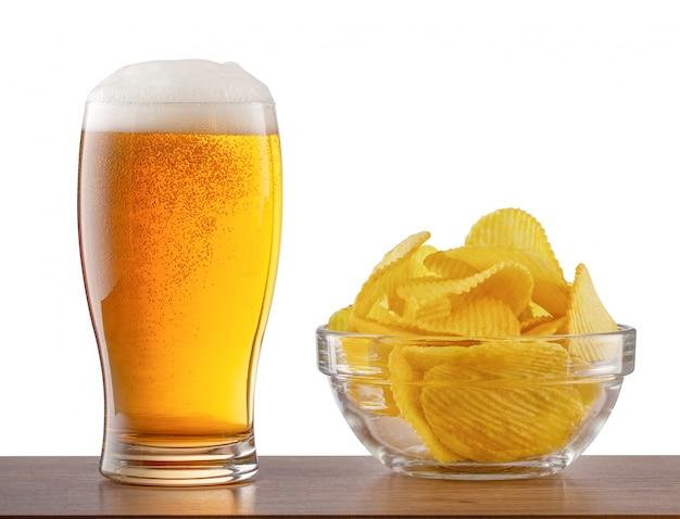 Copo de cerveja light e batatas fritas no balcão de bar Foto Premium