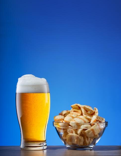 Copo de cerveja light e prato de batatas fritas em azul Foto Premium