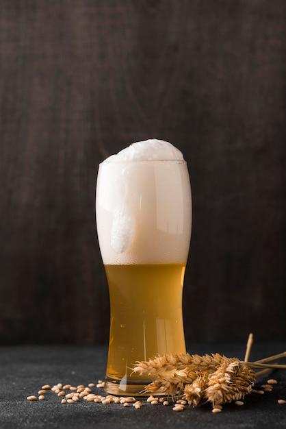 Copo de cerveja loira com espuma Foto gratuita
