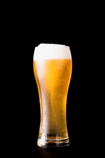 Copo de cerveja na frente de fundo preto Foto gratuita