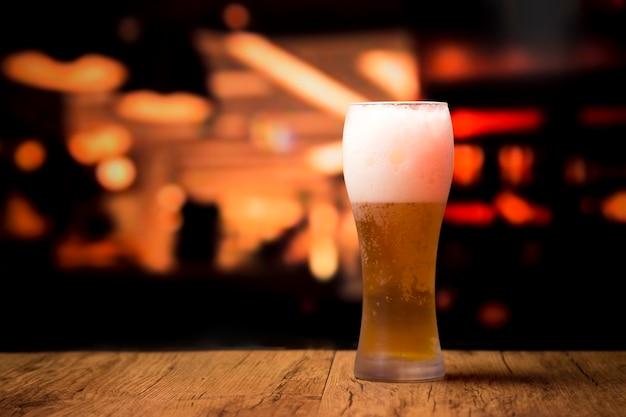 Copo de cerveja na frente do fundo desfocado Foto gratuita